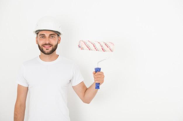 Retrato de um jovem decorador sorridente com barba por fazer e capacete segurando o rolo de tinta contra a parede branca