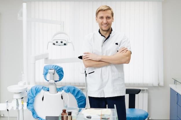 Retrato de um jovem dentista masculino positivo, de uniforme com as mãos cruzadas no consultório odontológico