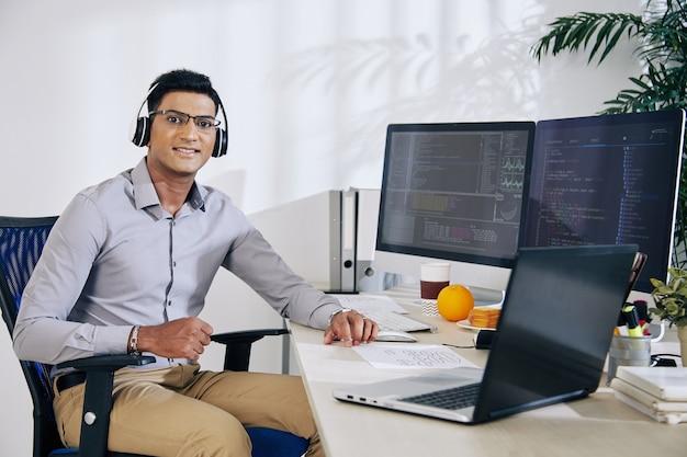 Retrato de um jovem desenvolvedor indiano de software sorridente de óculos, sentado na mesa do escritório com computadores e laptop