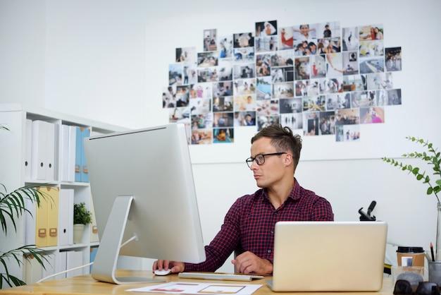 Retrato de um jovem designer de iu ou diretor de arte sério trabalhando em um projeto em sua mesa de escritório