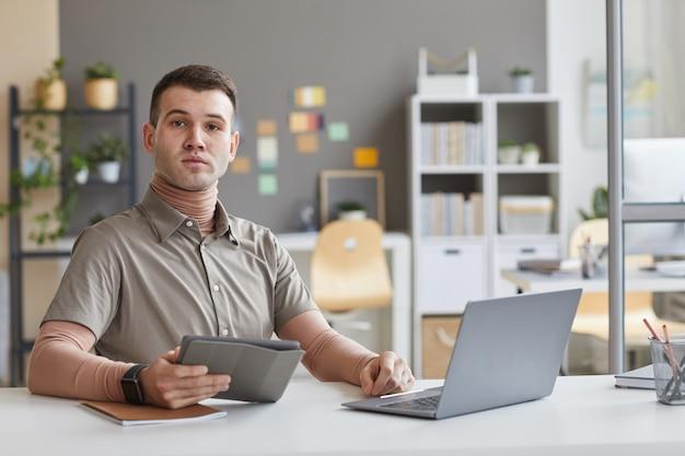 Retrato de um jovem designer gráfico sentado à mesa, olhando para a frente, usando tablet digital e laptop em seu trabalho