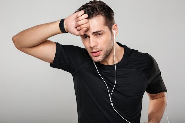 Retrato de um jovem desportista suado cansado em fones de ouvido