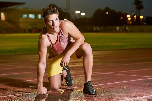 Retrato de um jovem desportista suor muscular posando no estádio