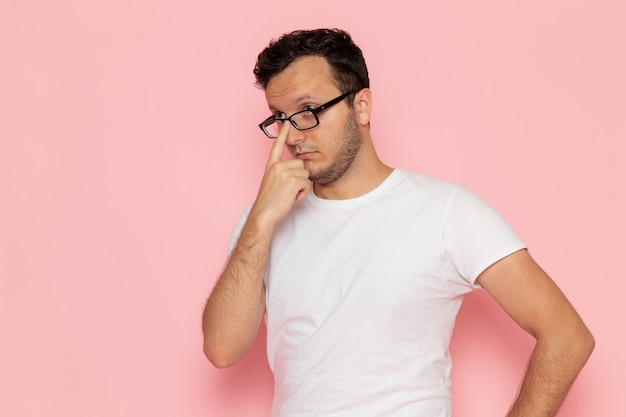 Retrato de um jovem do sexo masculino com camiseta branca e óculos de sol na mesa rosa.