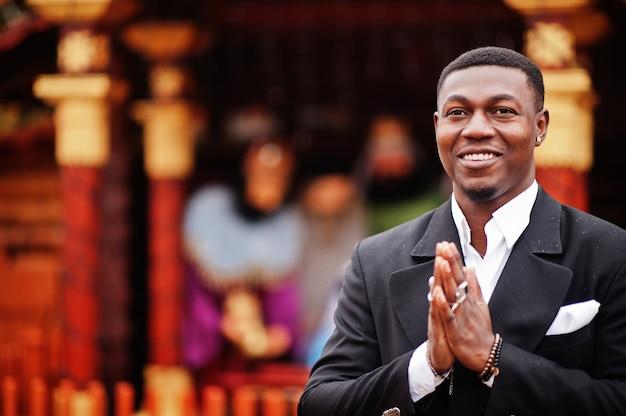 Retrato de um jovem e bonito empresário afro-americano de fato ficar e orar contra o presépio.