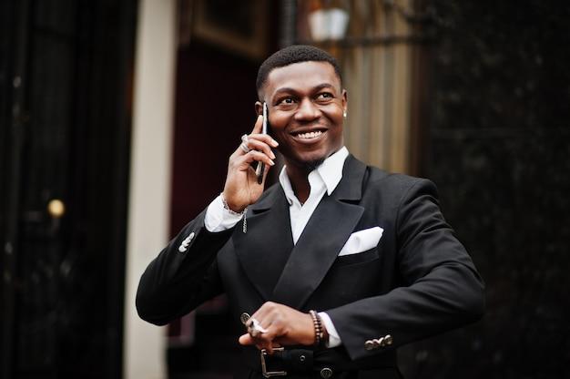 Retrato de um jovem e bonito empresário afro-americano em terno falar no celular, prepare-se para o encontro.
