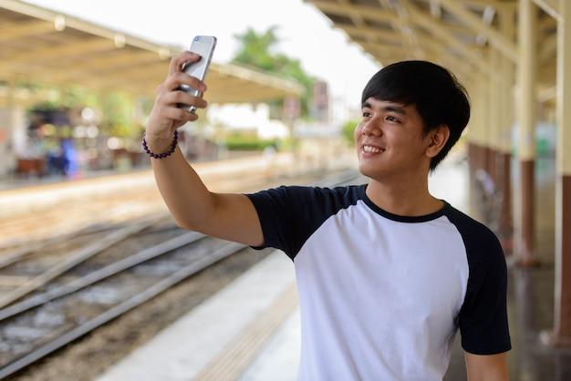 Retrato de um jovem e bonito turista filipino na estação ferroviária hua lamphong em bangkok