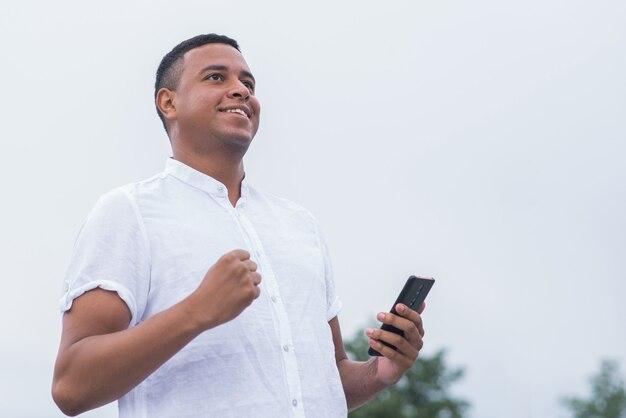 Retrato de um jovem e feliz afro-americano. homem feliz em pé e sorrindo, vitória, conquista