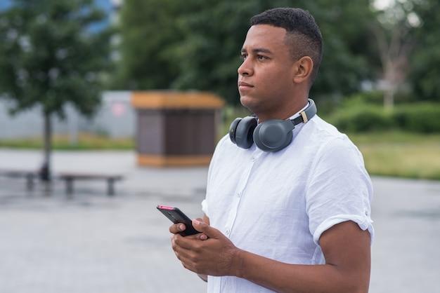 Retrato de um jovem e feliz afro-americano que usa um smartphone. conceito freelance