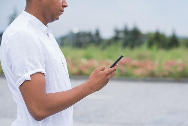 Retrato de um jovem e feliz afro-americano, usando um smartphone. freelancer, bate-papo, mensagens de texto