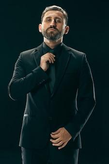 Retrato de um jovem elegante com corte de cabelo elegante, vestindo terno da moda posando sobre preto.