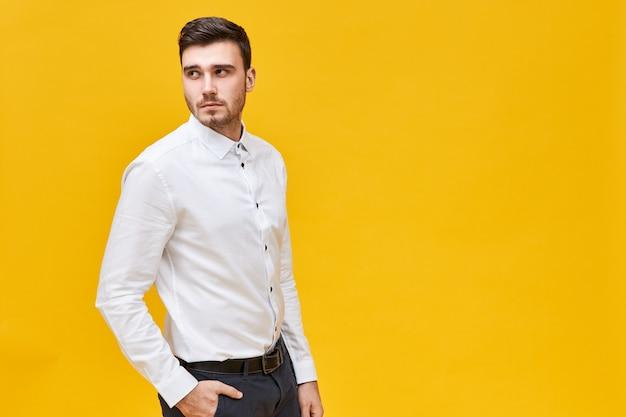 Retrato de um jovem elegante de cabelos escuros com barba por fazer e olhar sério, virando a cabeça para trás contra uma parede amarela em branco com espaço de cópia para o seu texto ou informações promocionais