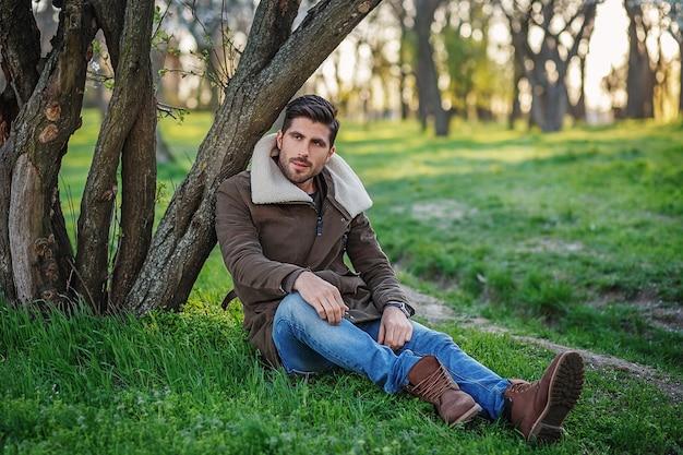 Retrato de um jovem elegante e atraente sentado na grama verde em um parque ao pôr do sol