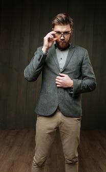 Retrato de um jovem elegante em óculos de pé e posando isolado no fundo preto de madeira.