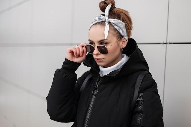 Retrato de um jovem elegante hipster com belos olhos com um penteado elegante com uma bandana em elegantes óculos de sol em um golfe de malha em uma jaqueta de inverno perto de uma parede branca. garota incrível.