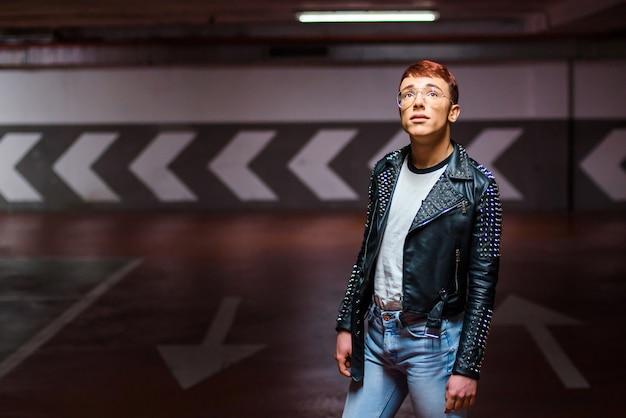 Retrato de um jovem elegante posando em um estacionamento subterrâneo