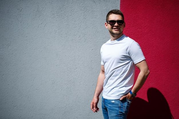 Retrato de um jovem elegante, um homem vestido com uma camiseta branca em branco de pé sobre um fundo de parede cinza e vermelho. estilo urbano de roupas, imagem na moda moderna. moda masculina