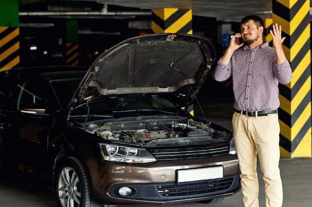 Retrato de um jovem em frente a seu carro quebrado e falando em seu telefone celular pede ajuda