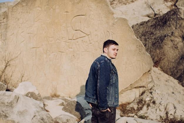 Retrato de um jovem em pé na parede de pedra