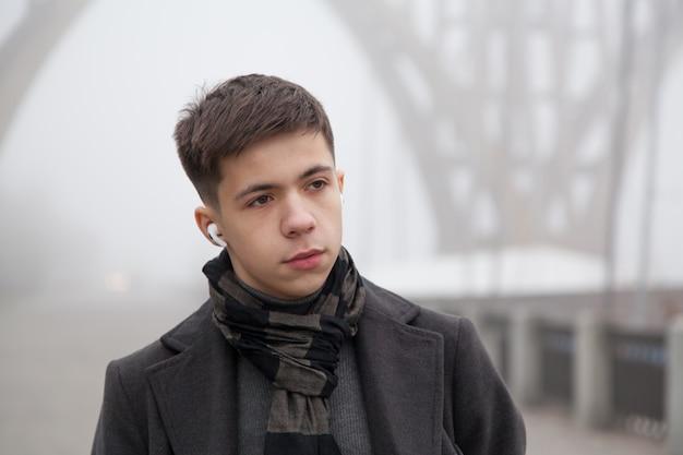 Retrato de um jovem em um passeio pela cidade, clima de inverno nevoento. foto em tons de cinza
