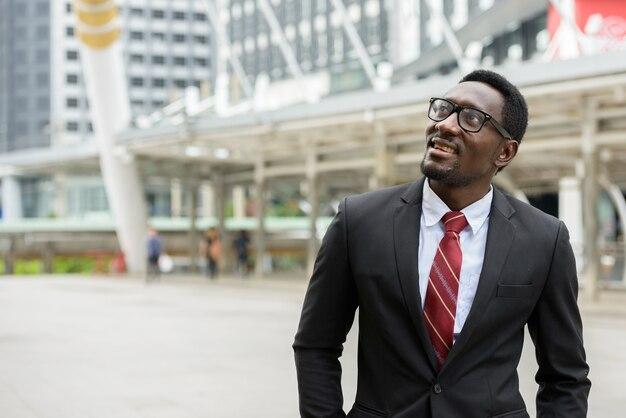 Retrato de um jovem empresário africano bonito em um terno contra a vista de um edifício moderno ao ar livre na cidade