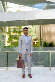Retrato de um jovem empresário africano bonito vestindo terno