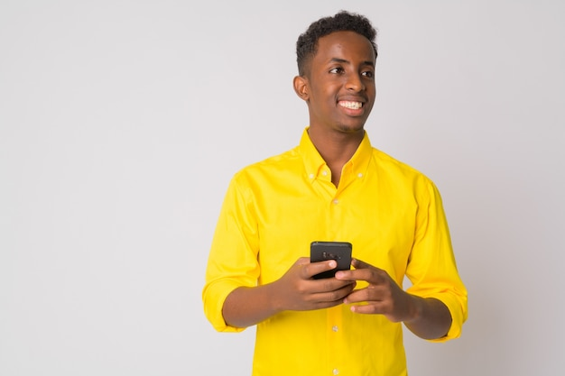 Retrato de um jovem empresário africano com cabelo afro, vestindo uma camisa amarela contra uma parede branca