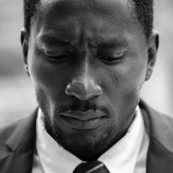Retrato de um jovem empresário africano estressado vestindo terno na cidade ao ar livre em preto e branco