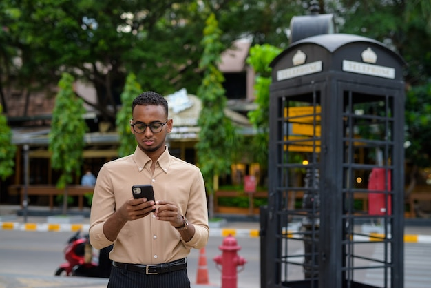Retrato de um jovem empresário africano negro vestindo roupas casuais ao ar livre na cidade e usando telefone celular