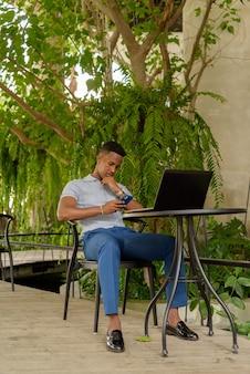 Retrato de um jovem empresário africano vestindo roupas casuais e sentado na cafeteria enquanto usa o computador laptop e o telefone celular enquanto se distanciando socialmente