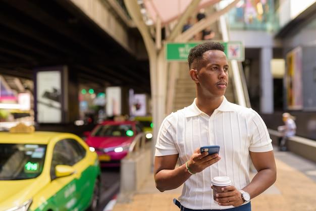 Retrato de um jovem empresário africano vestindo roupas casuais, enquanto usa o telefone celular e segurando a xícara de café na estação de táxi na cidade