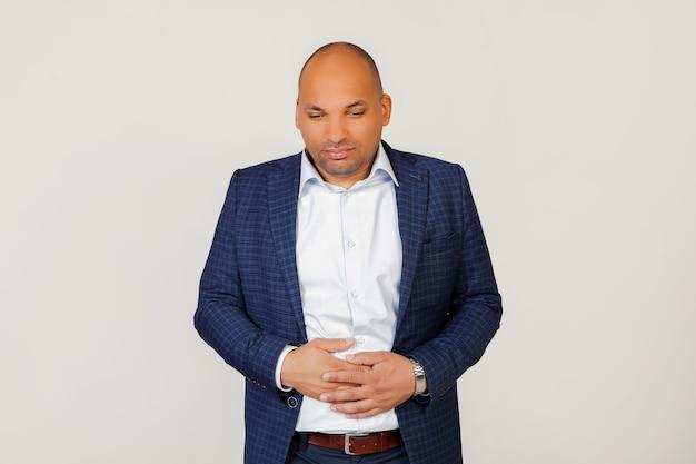 Retrato de um jovem empresário afro-americano doente, com uma mão na barriga devido a uma indigestão, passando mal. conceito de dor.