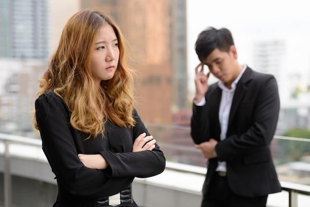 Retrato de um jovem empresário asiático e uma jovem empresária asiática juntos no exterior da cidade
