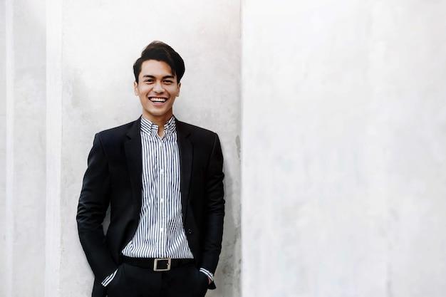 Retrato de um jovem empresário asiático sorridente em um terno casual.