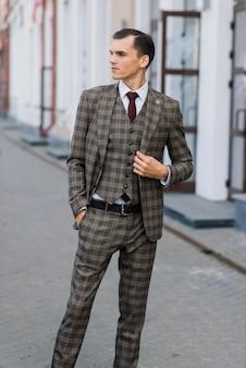 Retrato de um jovem empresário atraente na rua urbana, vestindo terno e gravata.
