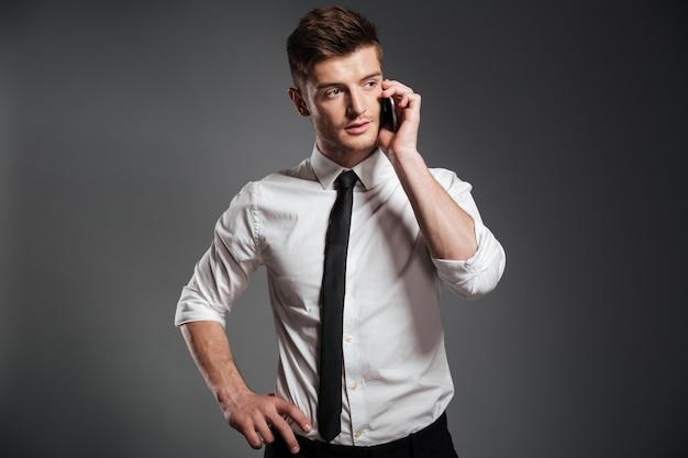 Retrato de um jovem empresário bonitão falando no celular