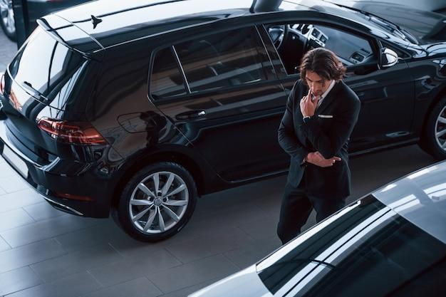 Retrato de um jovem empresário bonito de terno preto e gravata dentro de casa perto de um carro moderno.