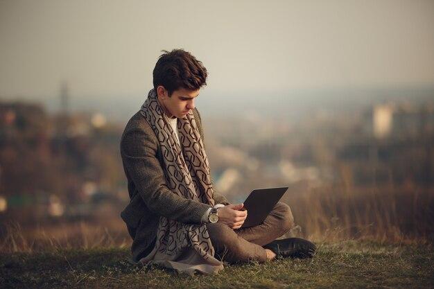 Retrato de um jovem empresário bonito e bem sucedido, sentado na grama, contra a silhueta da cidade à distância. imagem elegante de um homem com um casaco elegante.