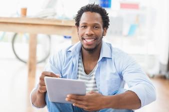 Retrato de um jovem empresário criativo rolagem no tablet