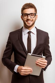 Retrato de um jovem empresário de sucesso está usando o tablet.