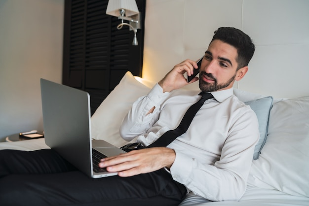Retrato de um jovem empresário deitado na cama e falando ao telefone enquanto trabalhava em seu laptop no quarto do hotel. conceito de viagens de negócios.