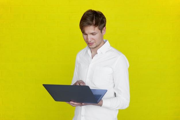 Retrato de um jovem empresário em camisa segurando e trabalhando no laptop, isolado em um fundo amarelo.