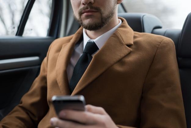 Retrato de um jovem empresário em um estilo empresarial de roupas no banco do passageiro