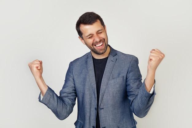 Retrato de um jovem empresário enérgico, desfrutando de sucesso com as mãos para cima