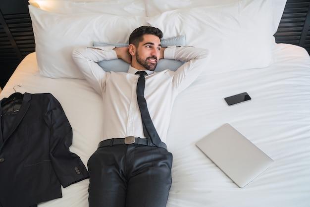 Retrato de um jovem empresário, fazendo uma pausa do trabalho e relaxando após um dia duro no quarto do hotel. conceito de viagens de negócios.