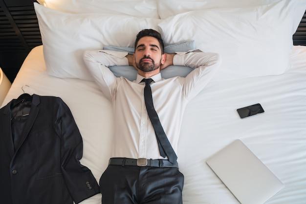 Retrato de um jovem empresário, fazendo uma pausa do trabalho e relaxando após um dia duro no quarto do hotel.