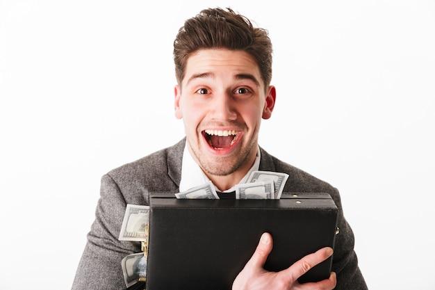 Retrato de um jovem empresário feliz, abraçando maleta