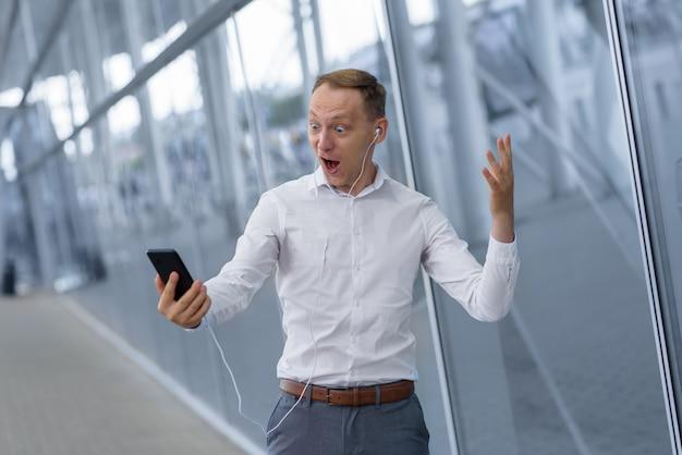 Retrato de um jovem empresário feliz em fones de ouvido. o homem recebeu boas notícias.