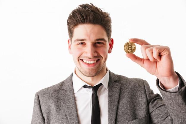 Retrato de um jovem empresário feliz mostrando bitcoin dourado