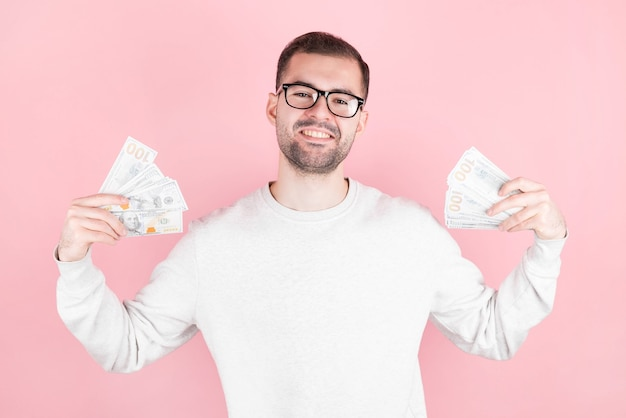 Retrato de um jovem empresário feliz segurando notas de dinheiro isoladas na parede rosa